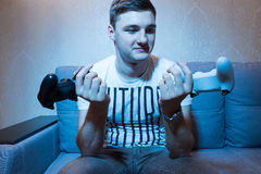 Young man holing two consoles and thinking which is the best Stock Images