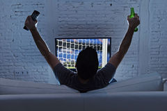 Young man home alone watching soccer or football game in television enjoying and celebrating goal. And victory holding beer bottle and TV controller gesturing Stock Photography