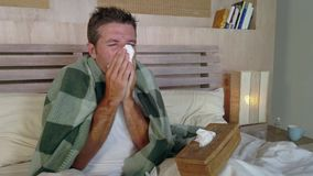 Young man at home bedroom lying in bed suffering grippe feeling unwell and sick sneezing and blowing nose covered with blanket stock video
