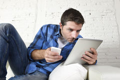 Young man at home couch working with mobile phone and digital tablet overworked suffering stress Royalty Free Stock Images