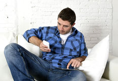 Young man at home couch working with mobile phone and digital tablet overworked suffering stress Royalty Free Stock Photography