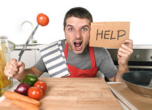 Young man at home kitchen in cook apron desperate in cooking stress. Young terrified man at home kitchen wearing cook apron showing help sign looking desperate Stock Images