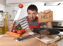 Young man at home kitchen in cook apron desperate in cooking stress. Young terrified man at home kitchen wearing cook apron showing help sign looking desperate Stock Photos