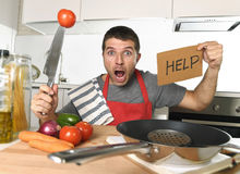 Young man at home kitchen in cook apron desperate in cooking stress Stock Photography