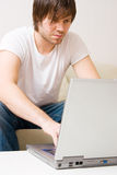 Young man home with laptop Royalty Free Stock Image