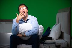 Young businessman under stress in the bedroom at night stock photo