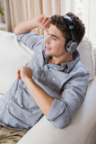Young man at home relaxing on the sofa. Listening to music royalty free stock photo