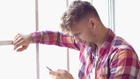 Young man at home saint valentine`s day concept chatting using smartphone. Young man at home saint valentine`s day standing near the window browsing smartphone stock video footage