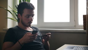 Young man at home shopping with credit card using smartphone at kitchen.  stock footage