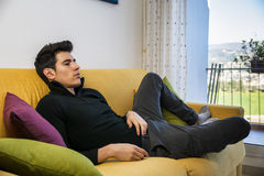 Young man at home sitting on couch watching Stock Images