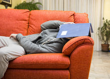 Young man at home sleeping instead of working or Stock Photos