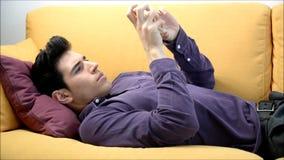 Young man at home on sofa, sending selfie falling asleep stock video