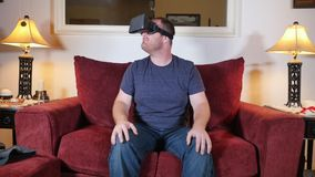Young Man at Home Uses a Virtual Reality Heads Up Unit. A man sitting on a sofa in his home uses a virtual reality heads up unit stock video