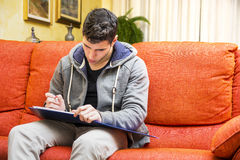 Young man at home writing on notebook Royalty Free Stock Photography