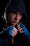 Young man in a hood. On black background Royalty Free Stock Photo