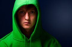 Young man in hood. Young man in green sweatshirt with turned up hood Royalty Free Stock Photo