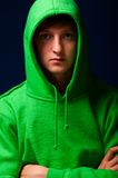 Young man in hood. Young man in green sweatshirt with turned up hood Royalty Free Stock Image