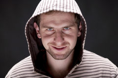 Young man with a hood. Portrait of young chuckling man with a hood on a black background Stock Images