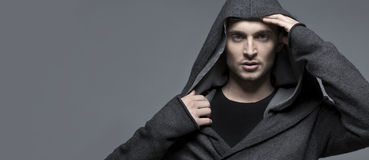 Young man in a hood, grey background. Man in a hood, bigger grey background Stock Photos