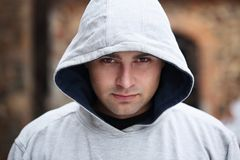 Young man in a hood. A handsome young man in a gray hood Stock Photo