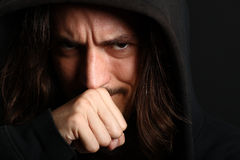 Young man in hood having dilemma. Guy with fist in front of mouth Stock Images