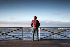 Young man in hood looking on the sea from pier Royalty Free Stock Image