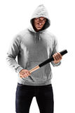 Young man with hood over his head holding a baseball bat symbolizing crime. Isolated on white background stock photo