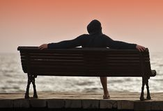 A young man with a hood sitting on a bench. Overlooking the ocean Stock Photos