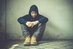Young man in hood sitting in room corner. Guy feeling sad and lonely Royalty Free Stock Photos