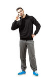 Young man in hood and sweatpants talking on mobile phone. Full body length isolated over white background Stock Image