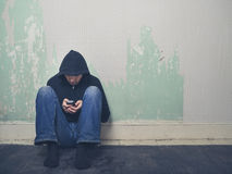 Young man in hood using smartphone Stock Images