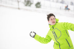 Young man in hooded jacket throwing snowball Royalty Free Stock Photo