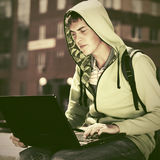Young man in a hooded sweatshirt using laptop. In city street Royalty Free Stock Photo