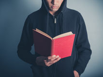 Young man in hooded top reading red book Stock Image