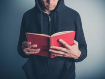 Young man in hooded top reading red book Stock Photos
