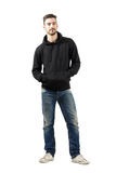 Young man in hoodie with hands in pockets smiling at camera Royalty Free Stock Photos