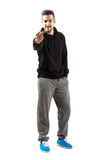 Young man in hoodie and sweatpants showing middle finger gesture Stock Photography