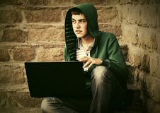 Young man using laptop on the steps. Young man in a hoodie using laptop on the steps Stock Photography