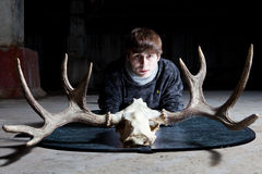 Young man with horned skull of deer Stock Photo