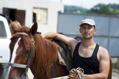 Young man with horse outdoor. Young man with brown horse outdoor Royalty Free Stock Photography