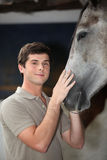 Young man with horse Stock Image