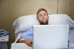 Young man in hospital room in bed using internet researching info on his own injury disease or sickness Stock Photography