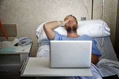 Young man in hospital room in bed using internet researching info on his own injury disease or sickness. Young man in hospital room lying in bed sick and injured Royalty Free Stock Image