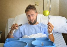 Young man in hospital room after suffering accident eating healthy apple diet clinic food moody and sad Stock Image