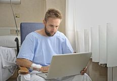 Young man in hospital room using internet researching info on his own injury disease or sickness Stock Images
