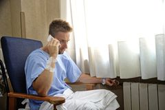 Young man at hospital room wearing patient pajamas sitting by the window talking on mobile phone Stock Photos