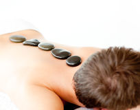 Young man with hot stones in a spa center Stock Image