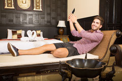 Young man in a hotel room taking a selfie Royalty Free Stock Photos