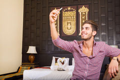 Young man in a hotel room taking a selfie Stock Photography