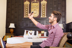 Young man in a hotel room taking a selfie Stock Photos